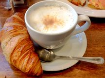 Cafe Latte and Croissant. A warm, frothy, cafe latte and a buttery, flaky croissant for breakfast Royalty Free Stock Images