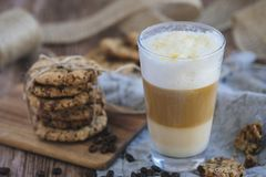 Cafe latte layered, with chocolate chip cookies. A high transparent glass filled with a layered cafe latte on a wooden table. The glass is on a linen cloth. Next stock photography