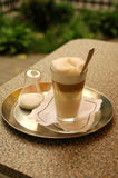 Cafe Latte in tall glass. Details of a Cafe Latte in a tall glass on a silver serving tray at an outdoor cafe Royalty Free Stock Image