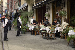 Cafe, Little Italy, New York City. Waiters stand at attention waiting to serve people eating lunch at outside tables with white table cloths, at an Italian Stock Photography