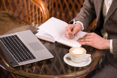 Cafe. Man on a coffee break with his laptop. Close-up Royalty Free Stock Photo