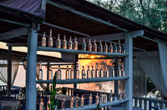 Cafe near the sea of rough planks with a lot of bottles. At dusk or at dawn stock images