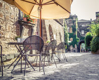 Cafe in old street in Europe with retro vintage effect. Cafe with tables and chairs in an old street in Europe with retro vintage Instagram style filter effect Royalty Free Stock Photos
