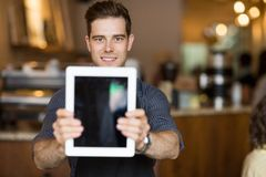 Cafe Owner Holding Digital Tablet In Restaurant. Portrait of male cafe owner holding digital tablet in restaurant Stock Image