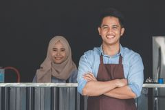 Cafe owner standing with crossed arms. Successful small business owner standing with crossed arms with partner at the background Stock Photo