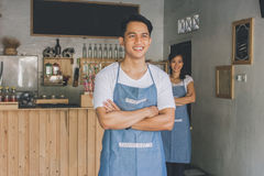 Cafe owner standing with crossed arms. Successful small business owner standing with crossed arms with partner at the background Royalty Free Stock Image