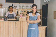 Cafe owner standing with crossed arms. Successful small business owner standing with crossed arms with partner at the background Royalty Free Stock Photography