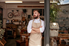 Cafe owner standing in the doorway of his coffee shop. Portrait of a cafe owner standing in the doorway of his coffee shop. Young waiter standing with his arms Royalty Free Stock Image