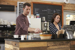 Cafe owners working behind the counter of their coffee shop Royalty Free Stock Images