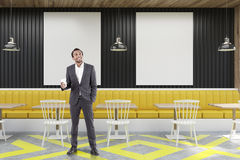 Cafe with posters, black and yellow, man Royalty Free Stock Photo