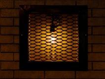 Cafe, pub or bar decorations. Old, vintage lamp behind bars on a Stock Image