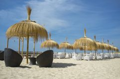 Cafe and restaurant armchairs with table and umbrella at beach Stock Photos