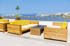 Cafe with sea view and empty sofas. Outdoor bar with wooden sofas and sea view Stock Photo