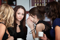 Cafe Secrets. In a group of four cute girls, a friend whispers something to another in a cafe Stock Photography