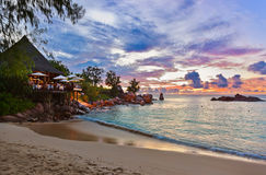 Cafe on Seychelles tropical beach at sunset Stock Photo