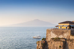 Cafe on the shore of the Mediterranean sea. Restaurant in Sorrento, on the shore of the Mediterranean sea against the background of mount Vesuvius stock photo