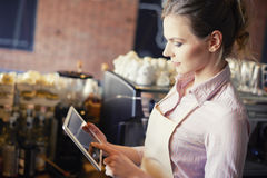 Cafe. Side view of waitress with digital tablet Stock Images