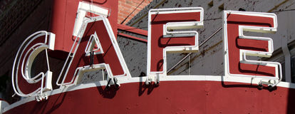 Cafe Sign. Tight view of red and white neon sign of oldtime cafe in small town America stock photography