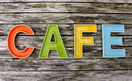Cafe. Sign made from colourful dishes on wood Royalty Free Stock Images