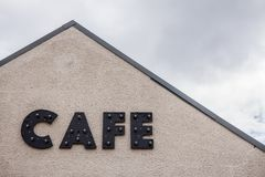 Cafe sign on the wall of a roadside cafe in scotland on a cloudy stock photos