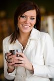 Cafe smile. Young woman poses in a cafe holding a cup Stock Photos