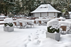Cafe with snow. Winter landscaper. Garden furniture melting after a snowstorm Stock Photos