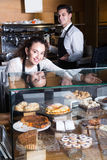 Cafe staff offering fancy. And sponge cakes for sale Royalty Free Stock Photo