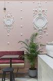 Cafe with stucco molding. Restaurant with white stucco molding on the pink wall and a  tiled floor. There is a tiled white rack, green plant in the pot, red sofa Royalty Free Stock Photo