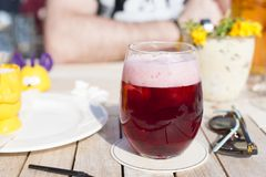 Cafe and sunlight. A glass of Belgian fruit beer. Alcohol on the table. stock photography