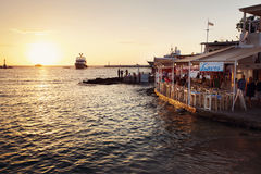 Cafe at Sunset, Mykonos Greece. Image of a cafe with tourists on Mykonos Beach at sunset with boat in the background stock photography