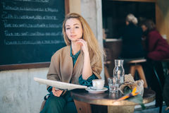Cafe table customer young woman coffee newspaper lifestule Royalty Free Stock Image
