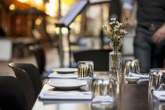 Cafe Table with Flowers. Cafe table in laneway.  Focus on Flowers Royalty Free Stock Photo