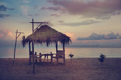 Cafe table in the form of huts on the beach at sunset Stock Photo