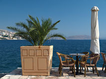 Cafe table on a harbourside with palm tree Stock Image