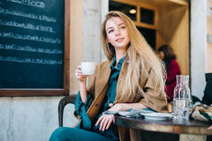 Cafe table young woman drinking coffee cup background lifestule. Girl with newspaper sitting table street restaurant blackboard Royalty Free Stock Photo