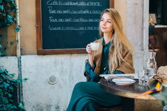 Cafe table young woman drinking coffee lifestyle blackboard background Royalty Free Stock Images
