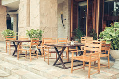 Cafe with tables and chairs in an old street in Europe with retro vintage Instagram style filter. Royalty Free Stock Images