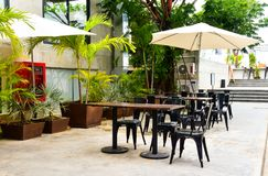 Chairs outside. Cafe tables and chairs outside with big white umbrella and plant Royalty Free Stock Photos