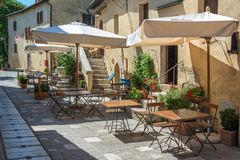 Cafe tables and chairs in a street in the village of Bagno Vignoni, Tuscany Italy. Cafe tables and chairs in a street in the village of Bagno Vignoni, Tuscany Royalty Free Stock Photo