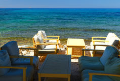 Cafe tables on coast of Crete island, Greece stock photography