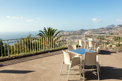 Cafe tables over Funchal,Madeira,Portugal. Empty cafe tables high over Funchal city and Atlantic ocean, Madeira, Portugal Stock Photo