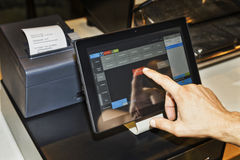 Cafe tablet arm. POS terminal in coffee cafe waiter's hand when serving customers and touching screen of a tablet with software interface to take order and print Royalty Free Stock Images