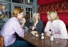 Cafe talk. Three people chatting in a cafe Royalty Free Stock Image