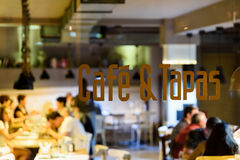 Cafe And Tapas Restaurant Sign. With Blurred People Background Royalty Free Stock Photos