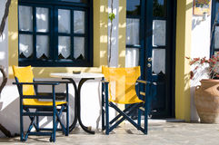Cafe or taverna or hotel setting greek islands. Cafe taverna and hotel setting with table and chairs and grape vines in the greek islands Stock Photo