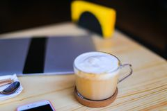 Cafe visitor made photo of table with cappuccino, laptop, smartphone. Professional photographer decided to work not at home, person took picture of wooden table royalty free stock photography