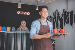 Cafe waiter holding tray with two cup of coffee. Happy asian male cafe waiter holding tray with two cup of coffee smiling Royalty Free Stock Images