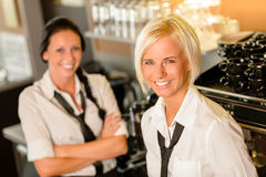 Cafe waitresses behind bar smiling at work. Break women colleagues Royalty Free Stock Image
