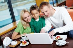 Cafe wi-fi. Parents and their male kid using the cafe wi-fi to surf the internet royalty free stock image