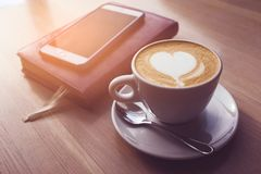 In the cafe on a wooden table is a Cup of cappuccino, laptop, phone, notebook, diary. Coffee mug. Businessman`s break. Businessma stock image